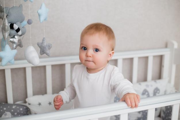 白い服を着た健康な赤ちゃんは子供のベッドに座っています。