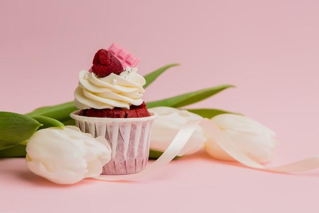 ピンクの空間にチョコレートケーキと白いチューリップ
