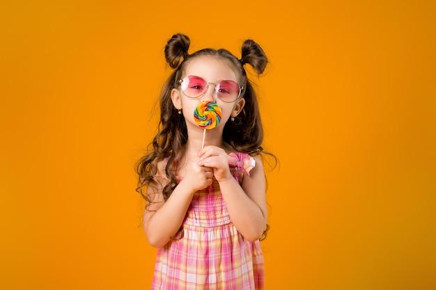 黄色のスペースでロリポップを舐める愛らしい女の子
