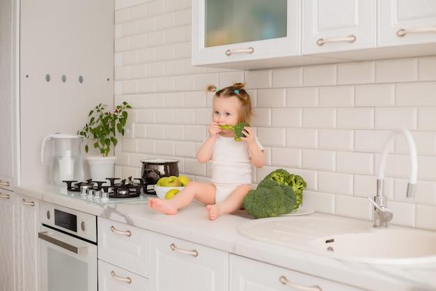 赤ちゃんは野菜で遊んで台所のテーブルに座っています。
