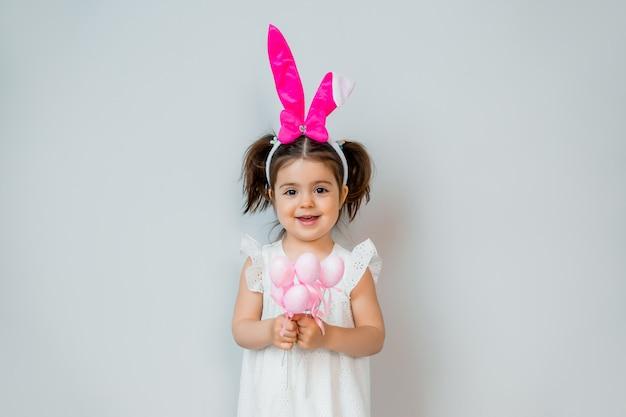 Милая маленькая девушка брюнет усмехаясь с ушами кролика на ее голове держа декоративные пасхальные яйца против светлой предпосылки. концепция пасхи, место для текста