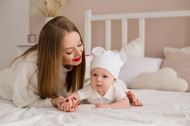 幸せな若い母親は自宅のベッドで幼児を抱擁します。