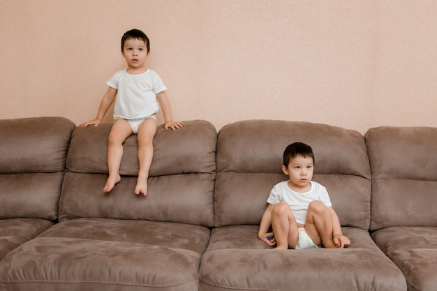 Дети играют в комнате дома. близнецы двух лет прыгают на диване