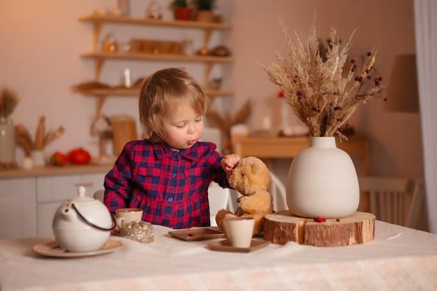 テディベアとキッチンで朝食を食べて笑っている女の赤ちゃん
