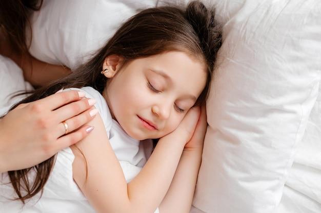 幸せな若い母は上からの眺め、ベッドで彼女の小さな娘を抱擁します。母と娘は自宅のベッドで休憩します。おはようございます!