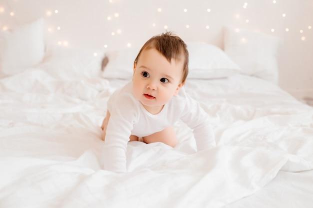ベッドで白いベッドリネンの上に座って笑っている白い服で健康な男の子