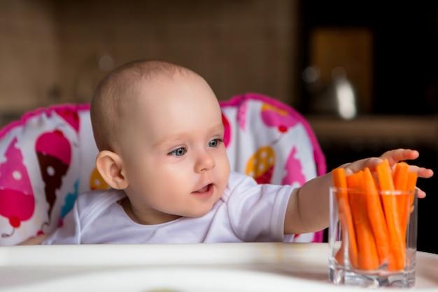 野菜を食べるチャイルドシートの赤ちゃん
