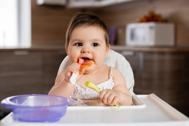 女の赤ちゃんは野菜のピューレを食べる子供の椅子に座っています。