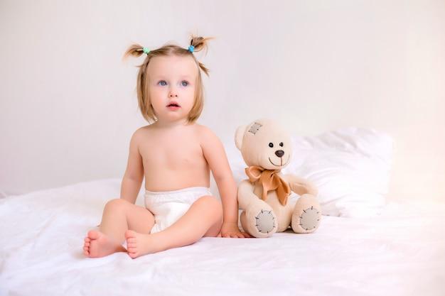 自宅のベッドに熊のぬいぐるみで座っているおむつで幼児の女の子