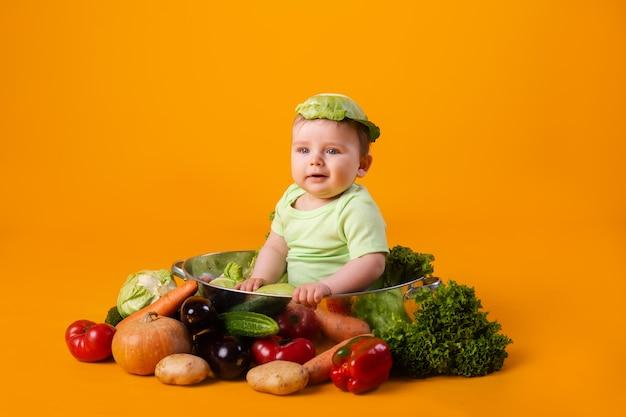 Мальчик в зеленом боди сидит в металлической миске с овощами. концепция сельскохозяйственного продукта