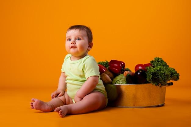 Мальчик сидит рядом с тазом со свежими овощами. концепция экологически чистых сельскохозяйственных продуктов
