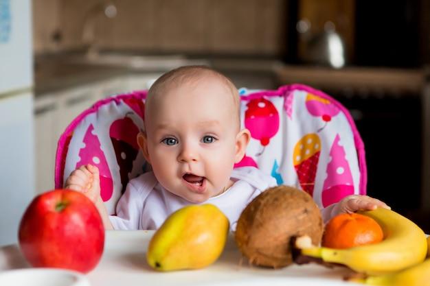 果物を食べると笑みを浮かべて高い椅子の子