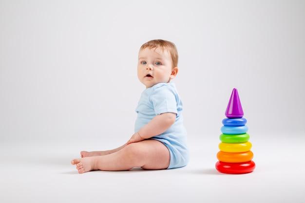 Милый малыш в синем боди играет с разноцветной пирамидой