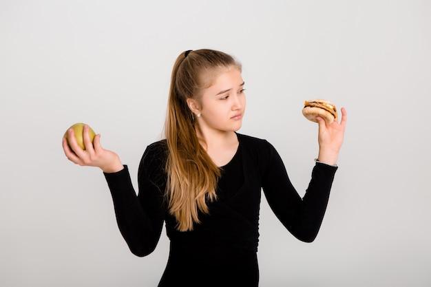 ほっそりした少女は、ハンバーガーとリンゴを保持しています。健康食品を選ぶ、ファーストフードはない