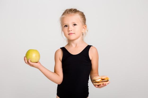 笑っている子供の女の子は、リンゴとハンバーガーを保持しています。健康食品を選ぶ、ファーストフードはない