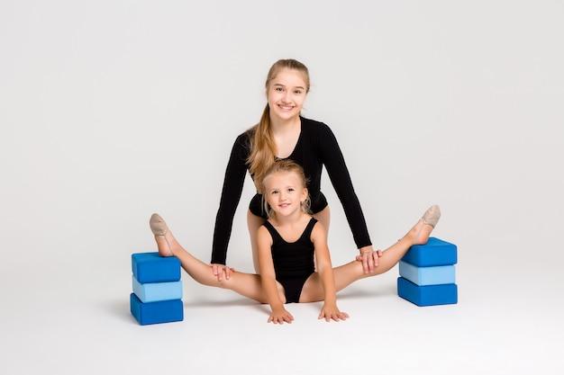 Молодая девушка занимается гимнастикой с маленькой девочкой