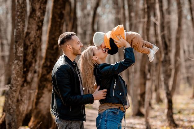 若い家族は春にベビーカーで幼児と一緒に公園を散歩します。幸せな親