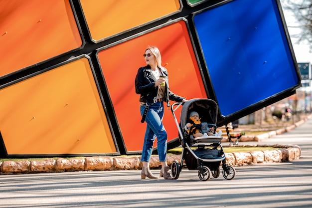 若い美しいママがベビーカーで幼児と一緒に公園を散歩して、コーヒーを飲む