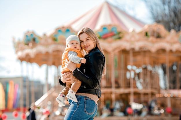スタイリッシュな若いお母さんが公園で赤ちゃんと一緒に歩きます。幸せなママ
