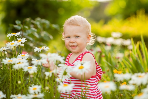 Девочка улыбается в летнем платье, гуляя на улице среди ромашек в саду