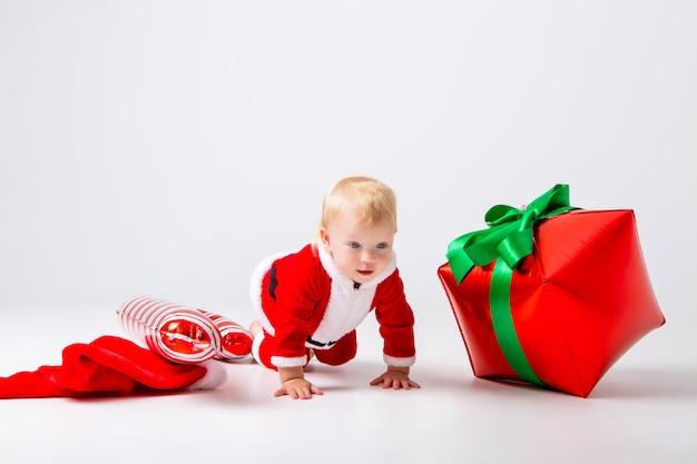 Малышка в новогоднем костюме с новогодними подарками на белой стене
