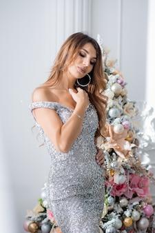 クリスマスツリーの近くのイブニングドレスの美しい若い女性。メリークリスマス