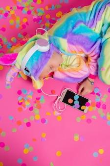 Счастливая маленькая белокурая девушка в кигуруми единорога слушает музыку держа в руке смартфон на розовой поверхности