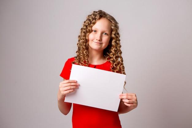 Предподростковая девушка с чистого листа бумаги или плаката