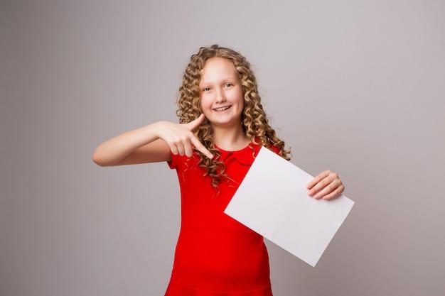 Предподростковый девушка, указывая пальцем на чистый лист бумаги или плакат