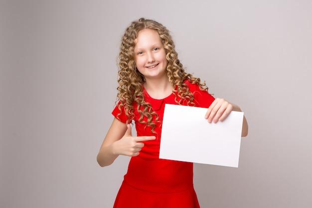 Предподростковый блондинка, указывая пальцем на чистый лист бумаги