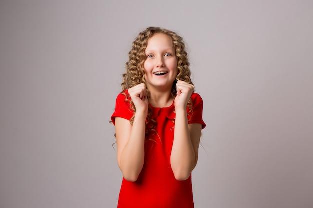 Симпатичная девчонка взволнована и полна радости новым сюрпризом