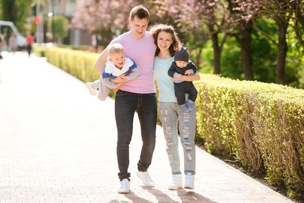 Молодая семья с двумя детьми на прогулке