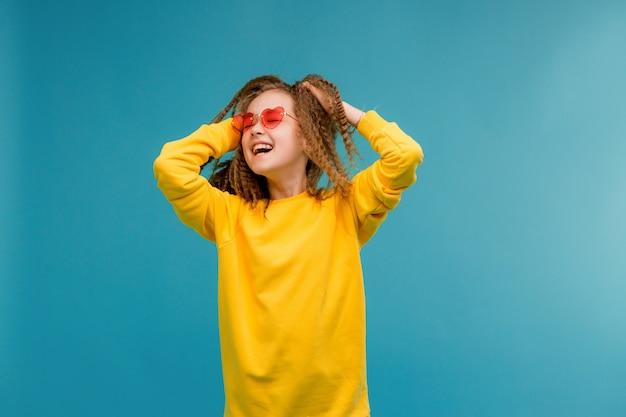 Предподростковый девушка в желтой одежде, улыбаясь