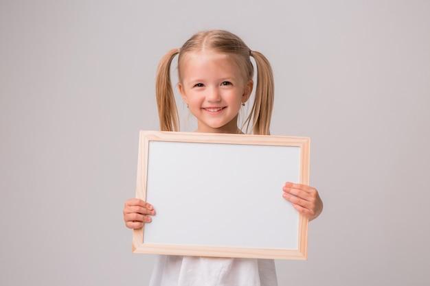 白い背景の上の白の描画ボードを保持している女の赤ちゃんの肖像画