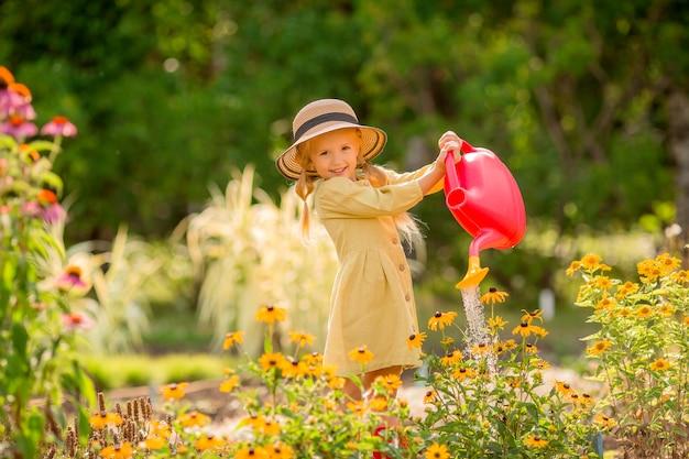 庭で花を水まき赤ゴム長靴の少女