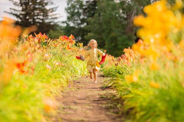 赤いゴム長靴と庭の赤い水まきに水をまく麦わら帽子の少女
