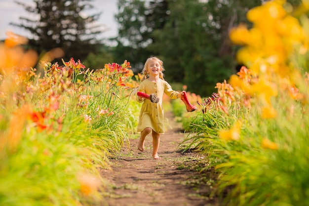 Маленькая девочка в красных резиновых сапогах и соломенной шляпе поливает красные цветы в саду