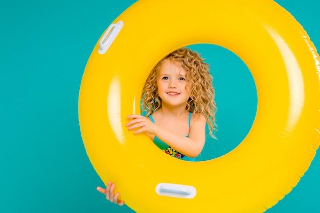 Счастливая девочка в купальнике с кругом на синем фоне