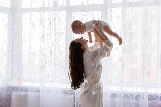寝室の窓の近くの赤ちゃんとママ