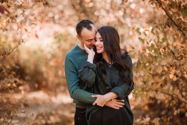 秋の森を歩く愛の若いカップル