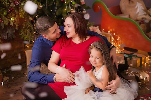 男とクリスマスツリーの横に妊娠中の女性