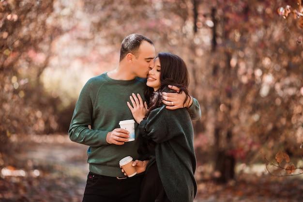 秋の森の散歩でコーヒーを飲むことを愛する若いカップル