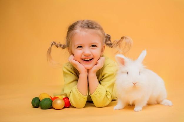 Маленькая девочка с пасхальным кроликом на желтом фоне