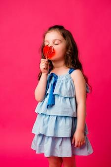 ピンクの背景笑顔に小さなブルネットの少女