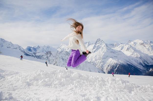 空の斜面でジャンプの若い女の子