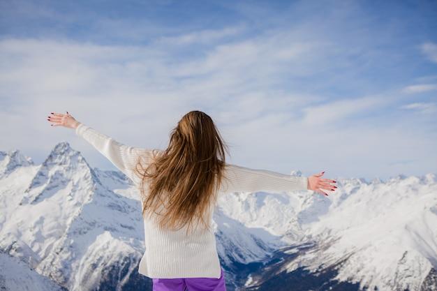 山を見て冬のスーツの少女