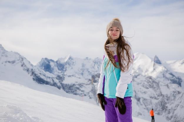 Молодая девушка в зимнем костюме улыбается в горах
