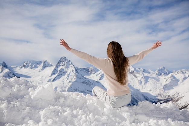 Молодая девушка в зимнем костюме смотрит на горы