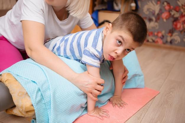 脳性麻痺の小さな子供は、運動をすることで筋骨格療法を受けています