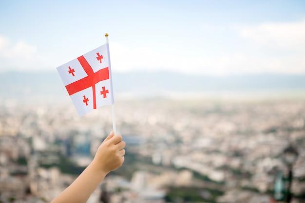 空を背景に子供の手でジョージアの旗